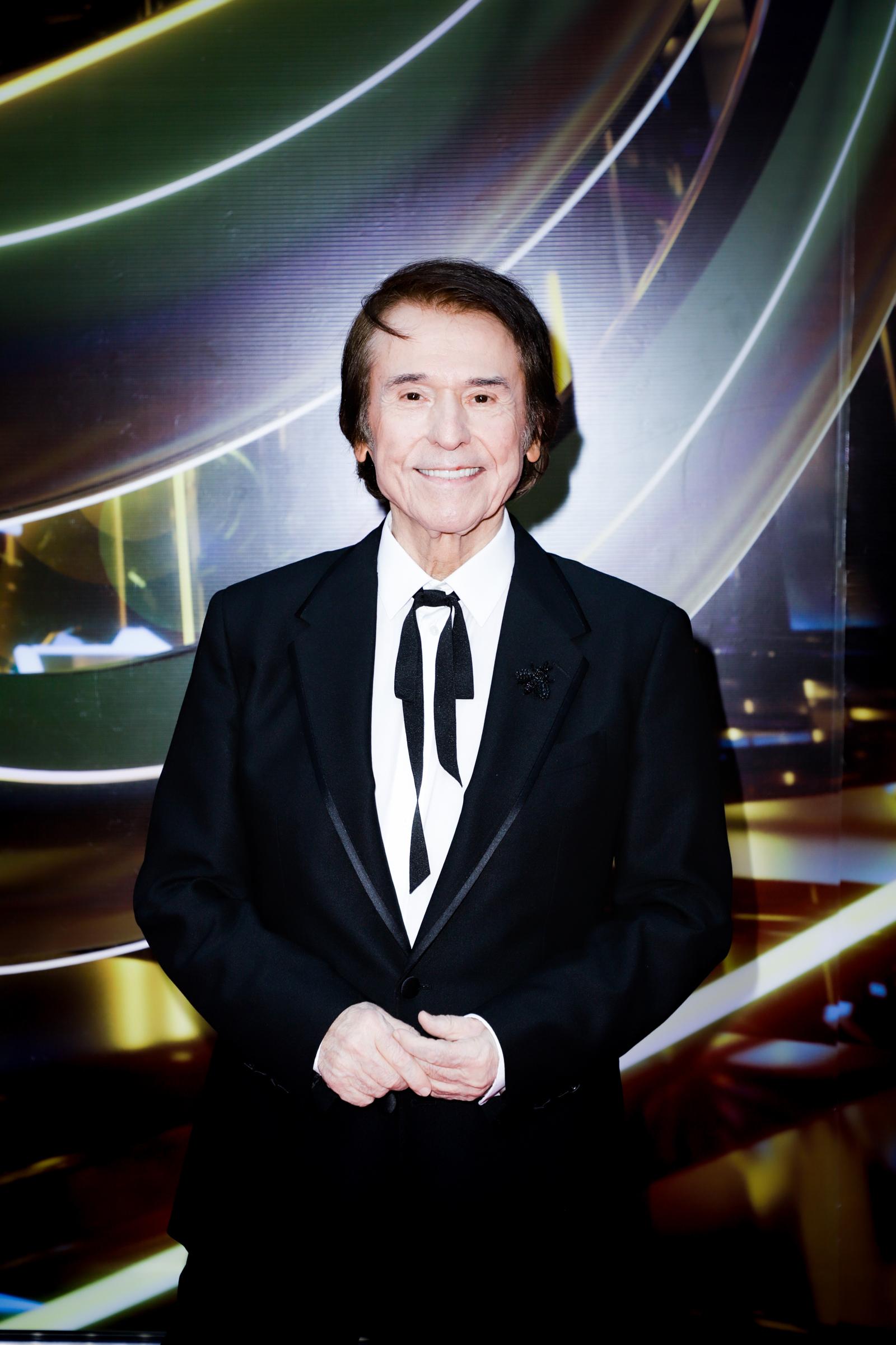 Con su habitual estilo elegante y clásico, el cantante español Raphael, quien fue reconocido por su trayectoria, seleccionó un traje negro con corbata a juego y camisa blanca. (Suministradas)
