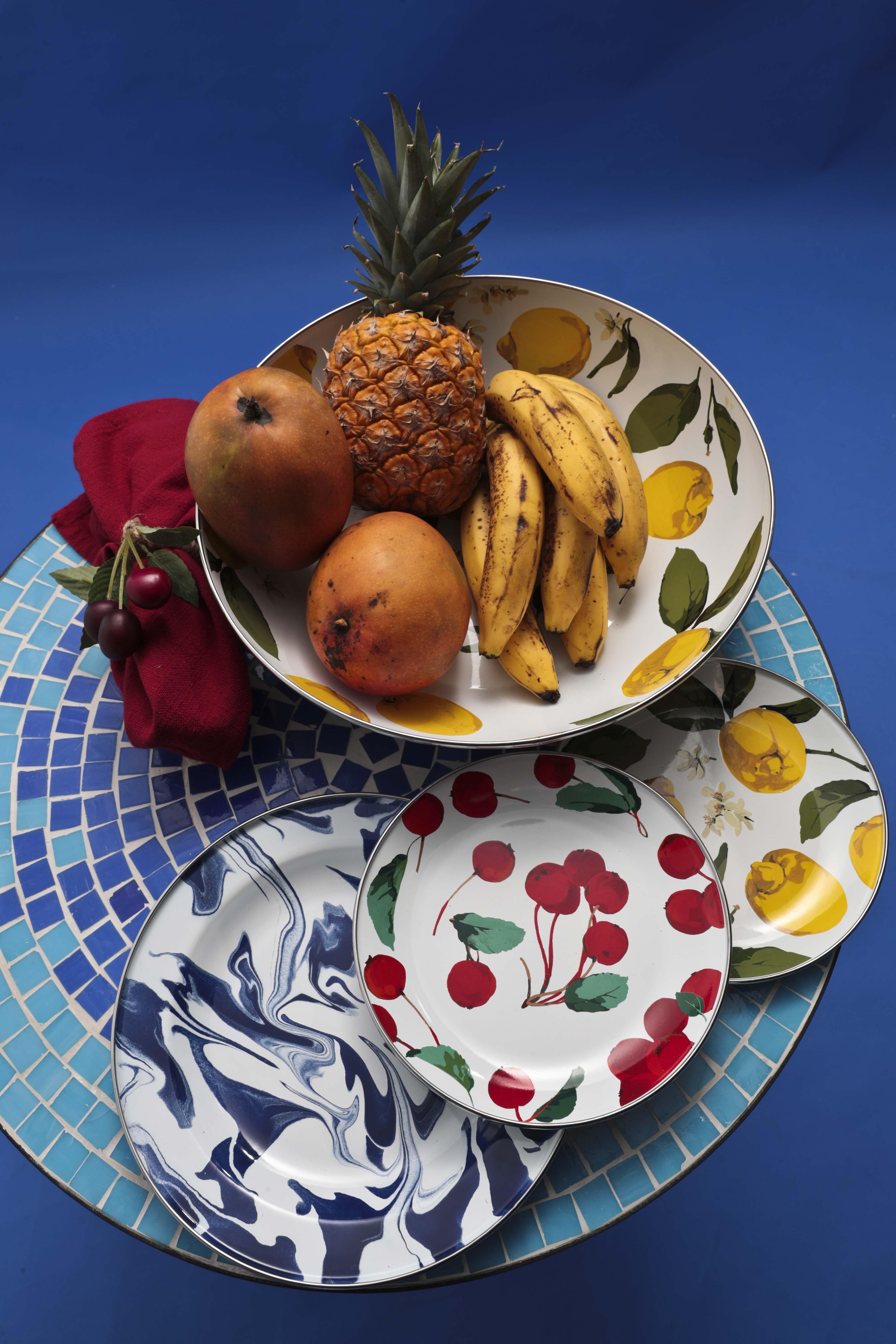Mesa con tope de mosaico, de Bed, Bath and Beyond; platos de acero inoxidable con diseños esmaltados de frutas e imitando mármol, servilleta de hilo y anillo para servilleta con acento de cereza, de Pottery Barn. (Foto Wanda Liz Vega)