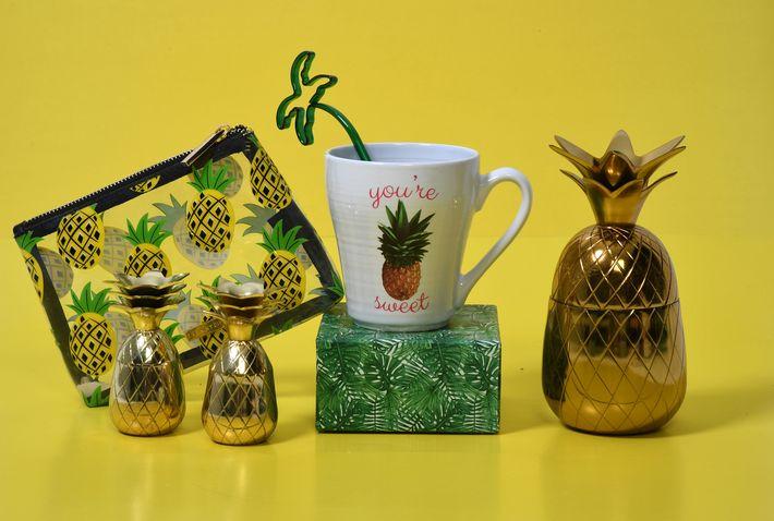 """Cartera pequeña, transparente, con estampado de piñas, de Macy's;  """"shot glasses"""" dorados, de Macy's; taza, de Macy's; pieza decorativa en madera y bronce, de TJ Max; y pieza decorativa dorada en forma de piña, de Macy's."""