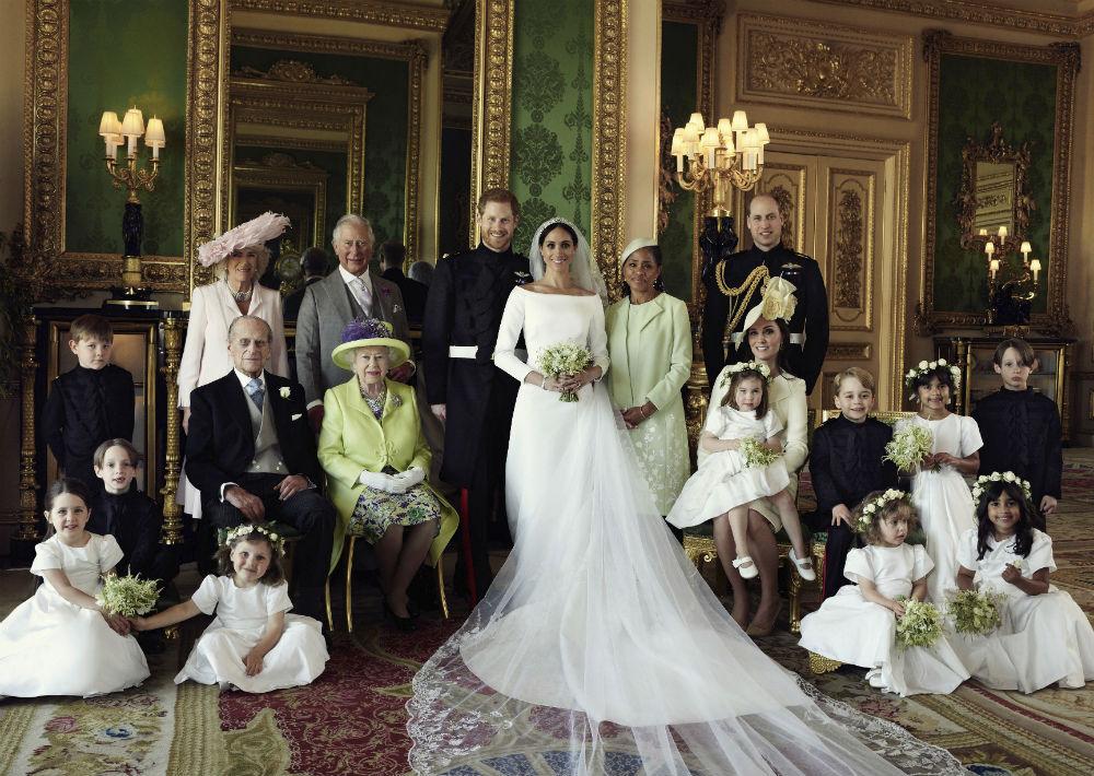De izquierda a derecha, atrás, Jasper Dyer, Camila, duquesa de Cornwall, el príncipe Charles, Doria Ragland y el príncipe William; en la fila central, Brian Mulroney, el príncipe Phillip, la reina Elizabethl II, Kate, duquesa de Cambridge, la princesa Charlotte, el príncipe George, Rylan Litt y John Mulroney; y abajo, Ivy Mulroney, Florence van Cutsem, Zalie Warren y Remi Litt. Al centro, el príncipe Harry y Meghan Markle.  (Alexi Lubomirski/Palacio de Kensington vía AP)