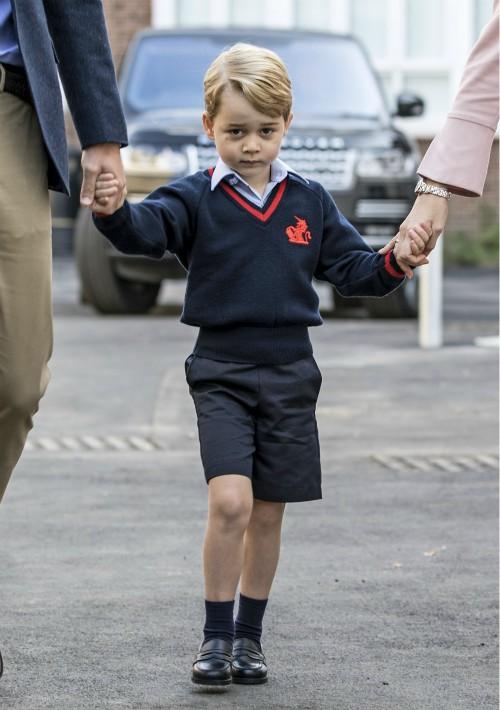 Con un gesto algo tímido y agarrado de la mano de su padre, una foto de la primera vez que el príncipe George  llegó al colegio con un adorable atuendo veraniego: bermudas y jersey azul marino, camisa Oxford y mocasines negros. (Foto: EFE)