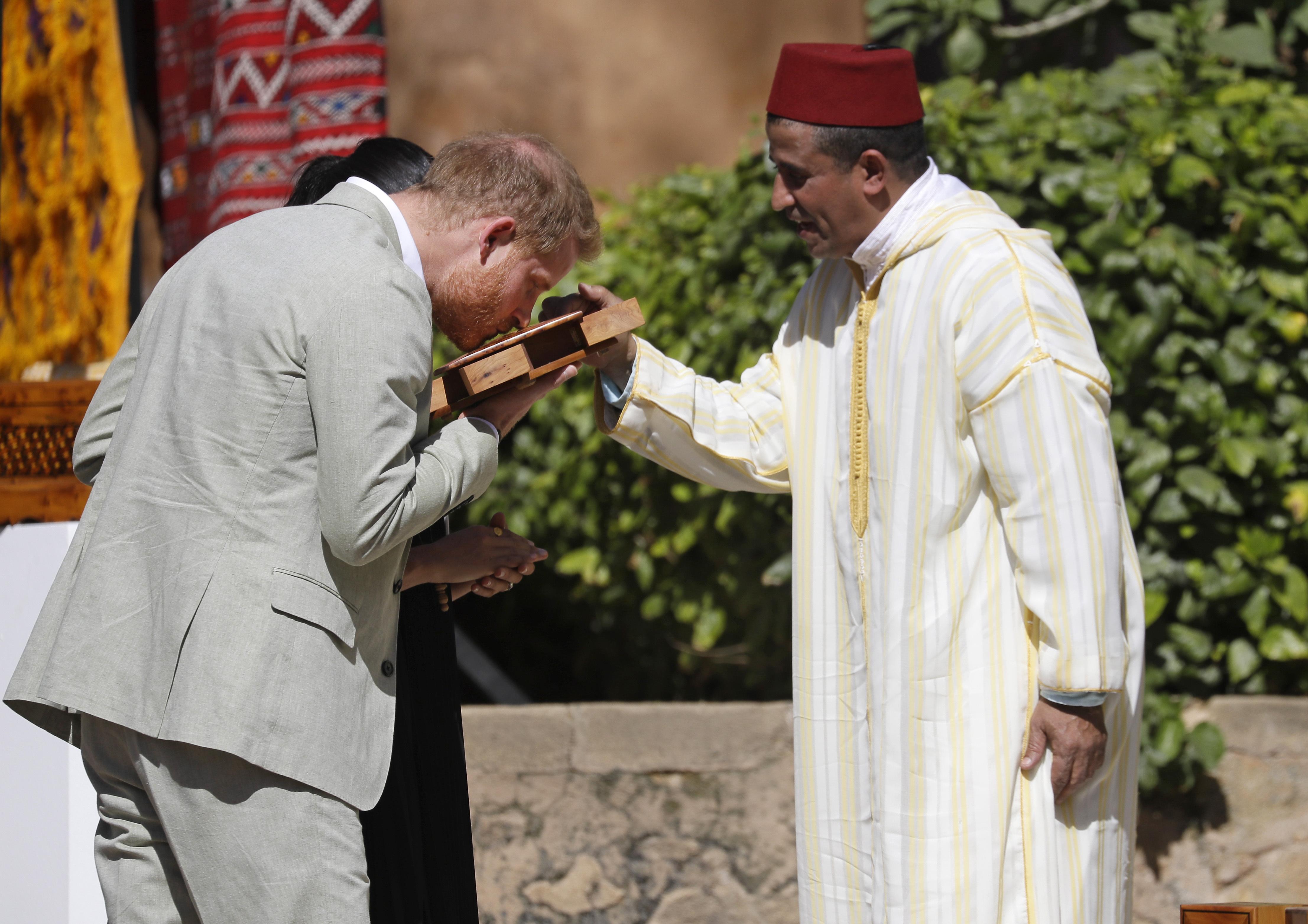 El príncipe Harry huele una caja de madera de cedro como parte de su visita a Rabat. (AP)