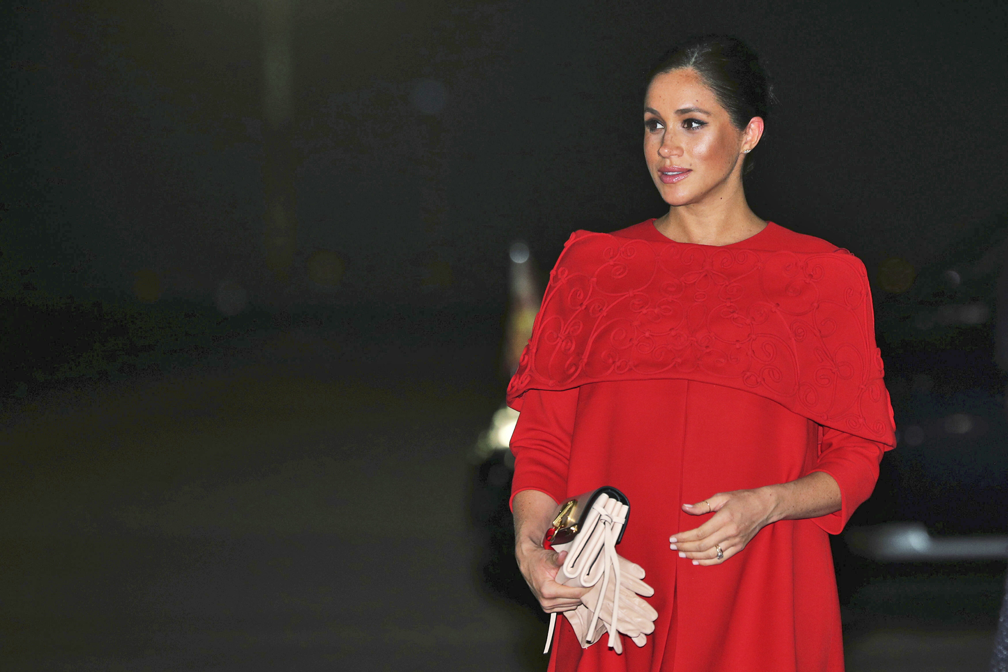 Meghan optó por un vestido rojo de Valentino por encima de las rodillas, con una discreta capa bordada y con un corte que marcaba su, ya abultada barriguita. (AP)