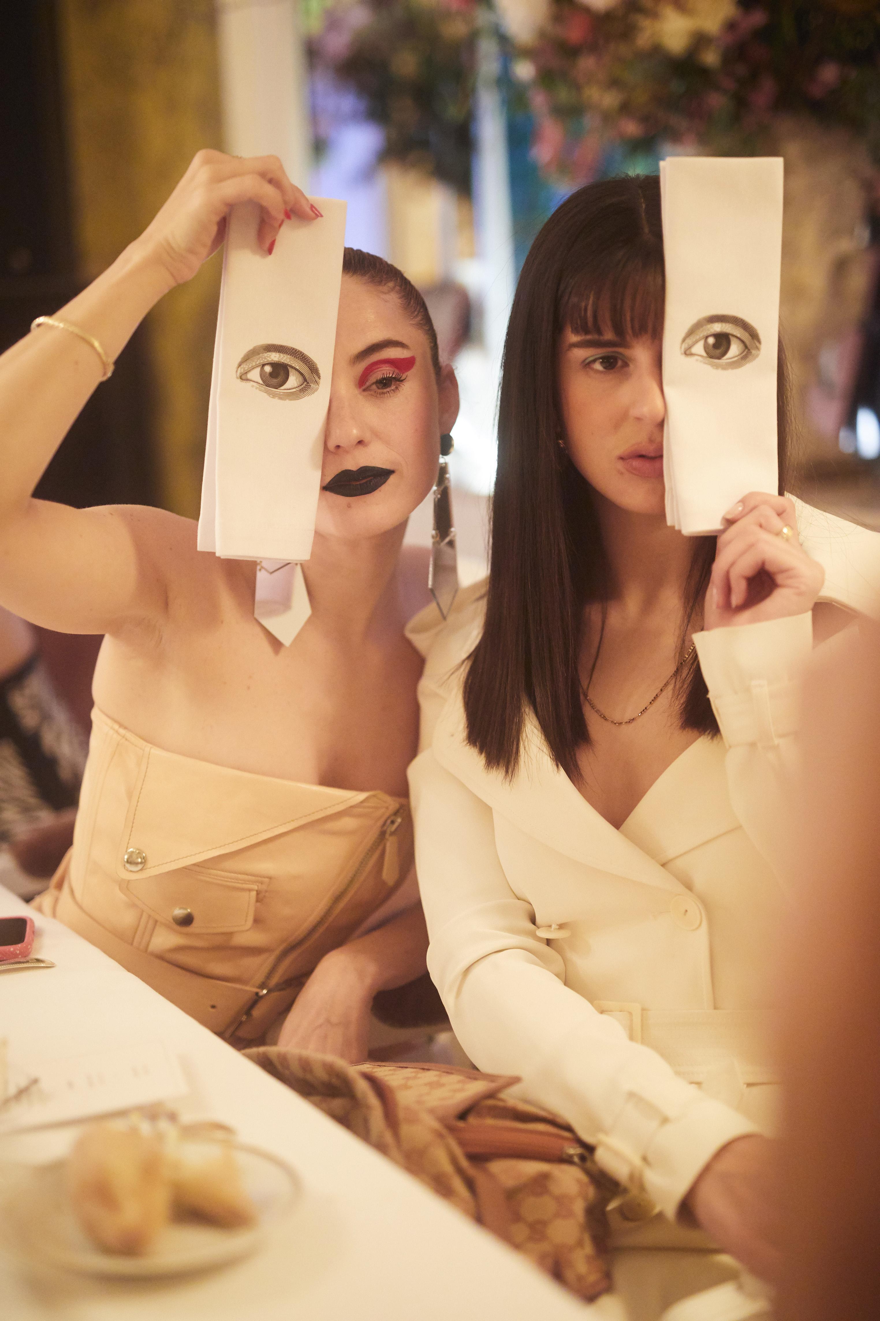 Dos invitadas con las servilletas que se usaron en la cena, en la que el detalle principal era un ojo. Fotos Paul Blind, Francois Goizé, Valentin Lecron.