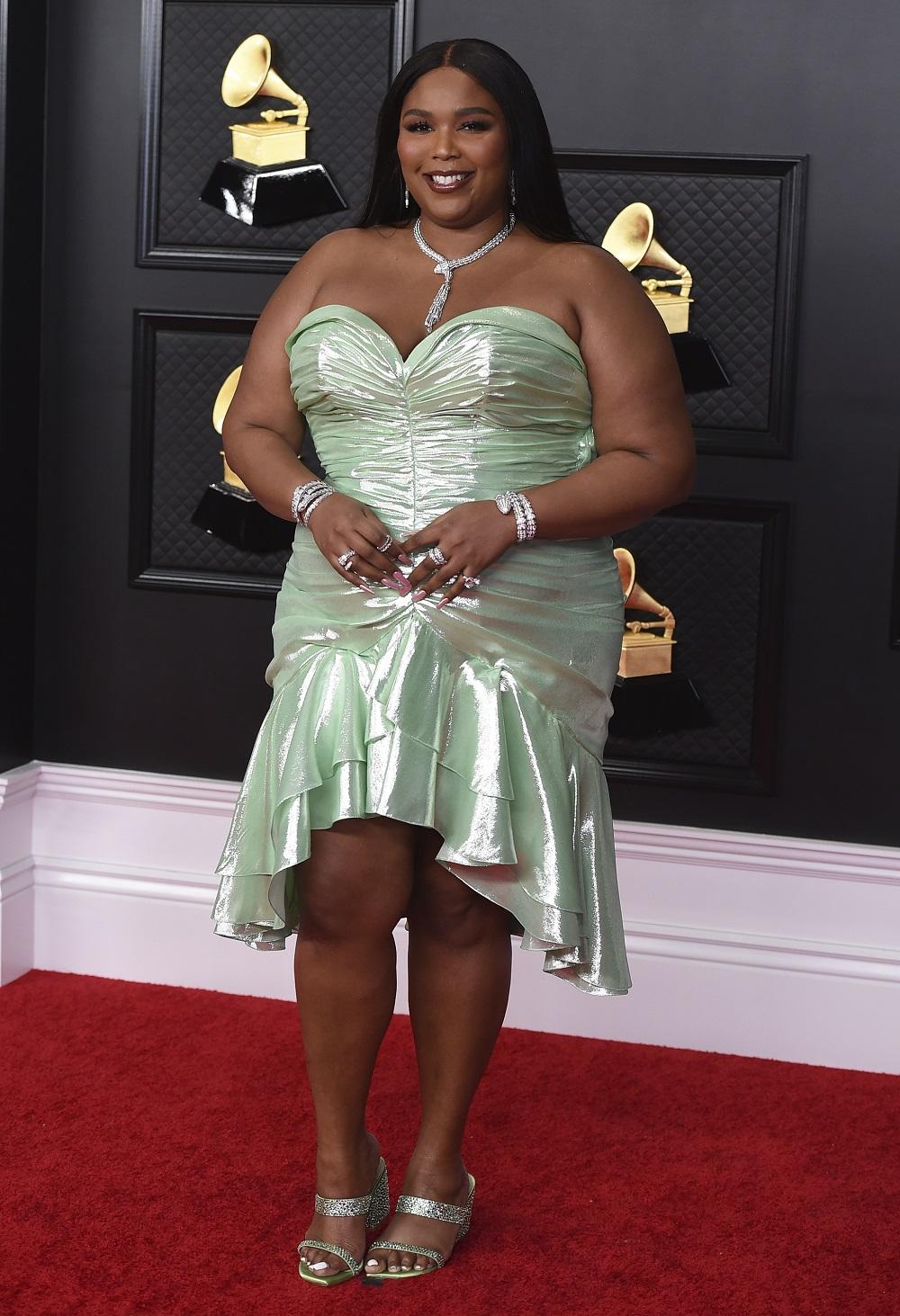Lizzo lució un vestido corto sin tirantes de espuma de mar con pliegues de Balmain. (AP)