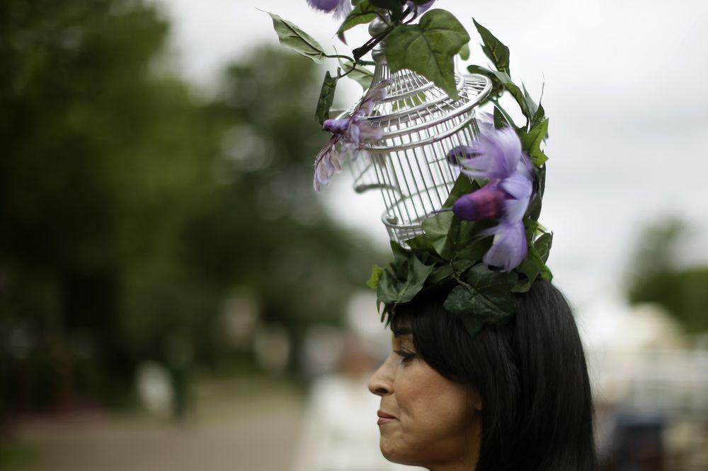 La invitada luce un sombrero original que simula una jaula de pájaros, abrazada por hojas y pájaros de color lila y acentos morados. (Foto: AP)