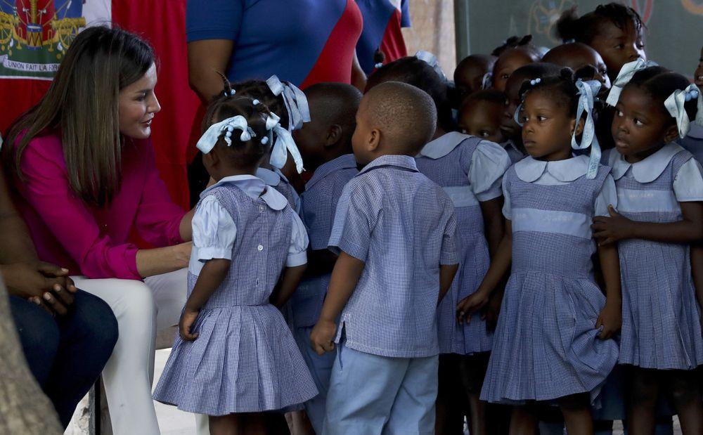 La reina Letizia durante su visita al colegio de las hermanas de San Vicente de Paul, que atiende a niños pobres en el barrio de Cité Soleil, una de las zonas más deprimidas de la nación antillana. (EFE)