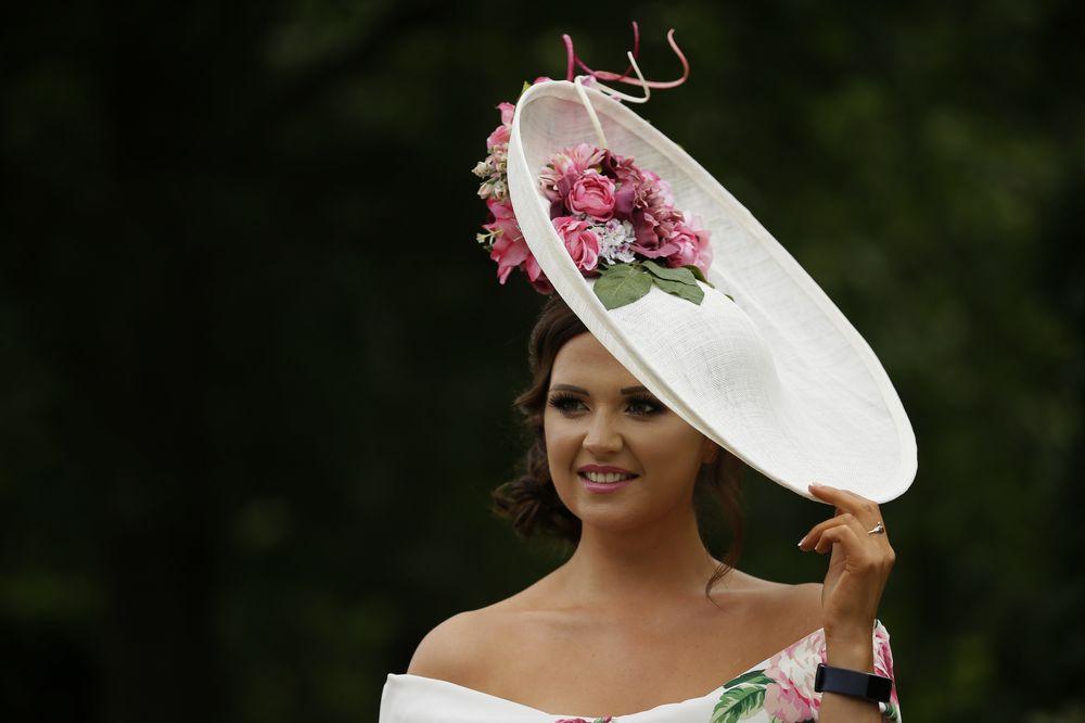 La invitada lleva un sombrero puesto de forma asimétrica, decorado con flores de distintas tonalidades de rosado. (Foto: AP)