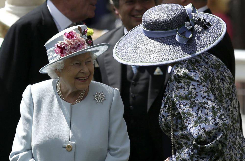 La reina conversa con una invitada que lleva un sombrero de gran amplitud y decoración leve. (Foto: AP)