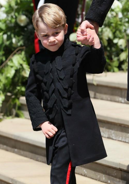 Para la boda de su tío, el príncipe Harry, y como parte del cortejo de pajes, George lució unos pantalones negros con una línea roja a los lados y una chaqueta  combinada en el mismo color. (Foto: EFE)