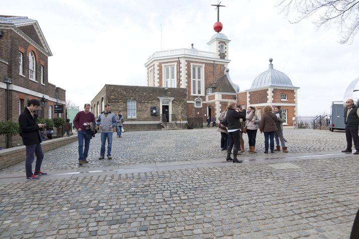 Turistas se alinean alrededor de la marca del Meridiano 0 o Meridiano de Greenwich, en Londres.