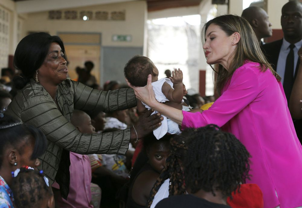 La reina Letizia (derecha) coge a un bebé en brazos durante su visita al colegio de las hermanas de San Vicente de Paul. (EFE)
