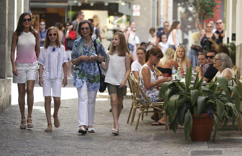 Letizia y sus hijas con pantalones cortos de color claro, y la reina Sofía con pantalón largo blanco y una blusa en tonos azules. (EFE)