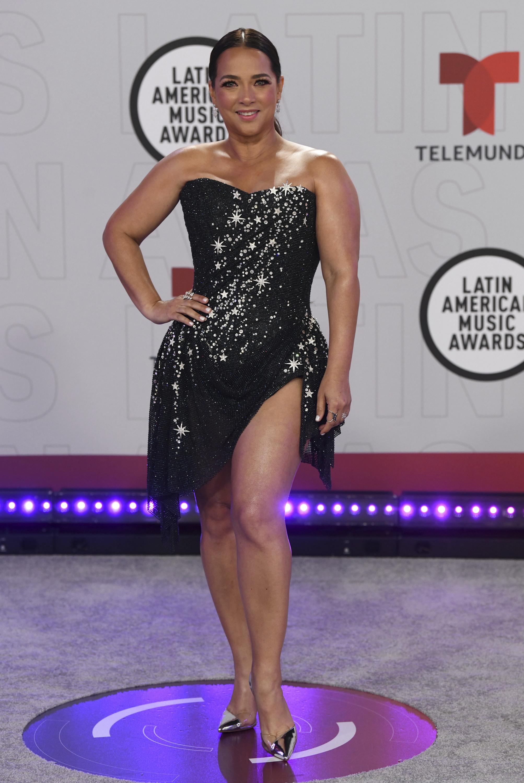 """Adamari López, presentadora del programa mañanero """"Hoy día"""" prefirió un estilo elegante compuesto por un minivestido de tul negro con detalles plateados. (AP)"""