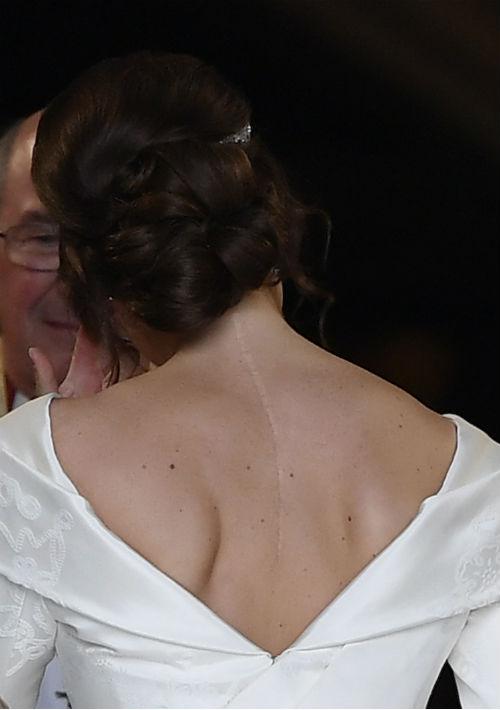 El vestido de Eugenie se cortó en una V profunda en la parte delantera y trasera, una característica solicitada por la novia que reveló una cicatriz vertical de su cirugía a los 12 años para corregir la escoliosis. Ella ha dicho anteriormente que es importante que las personas muestren sus cicatrices. (AP)