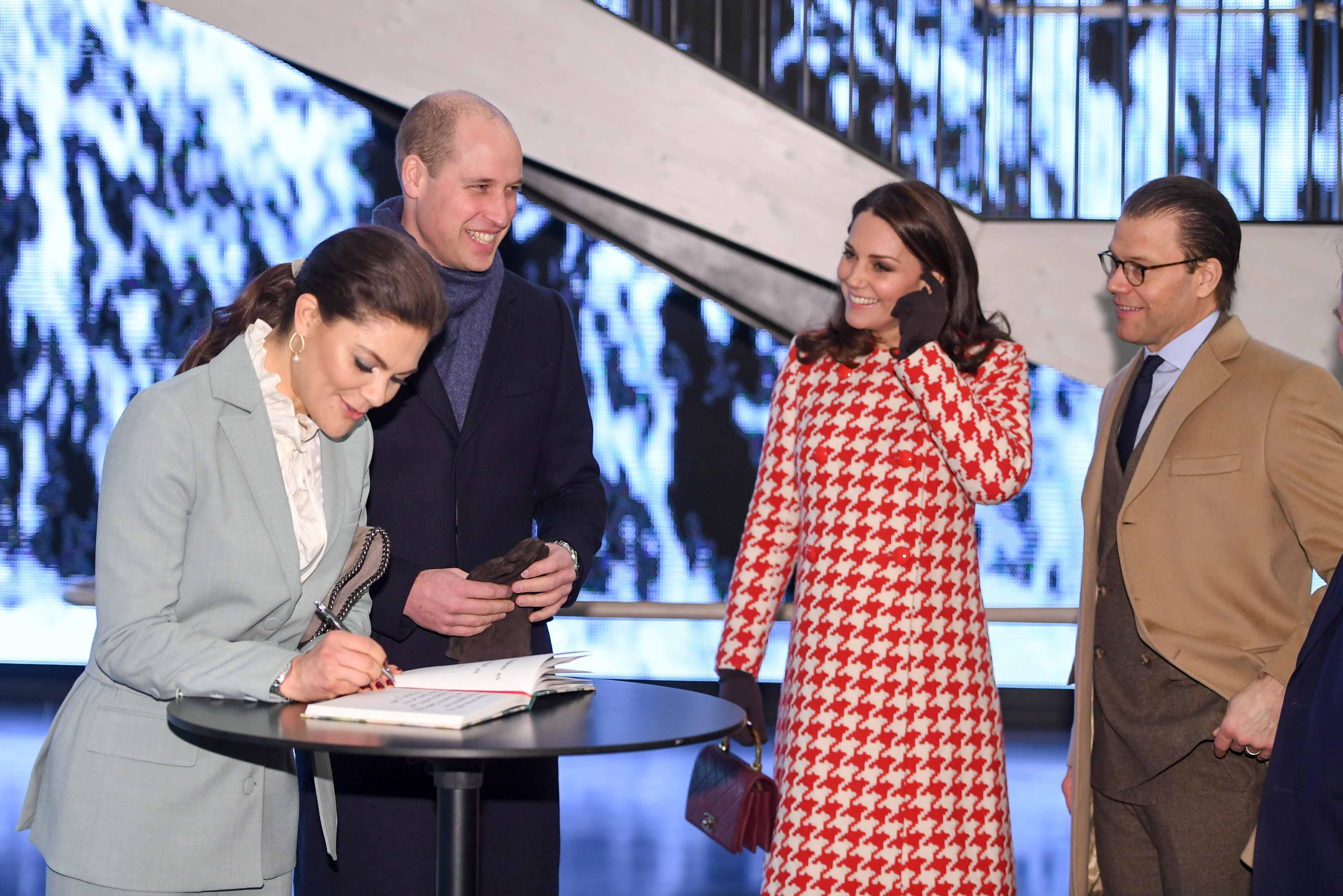 La princesa Victoria, heredera al trono de Suecia, firma el libro de visitas del Instituto Karolinksa  en Solna, acompañada por el príncipe William, Kate Middleton, y su esposo el príncipe Daniel. (Foto: Henrik Montgomery/TT via AP)