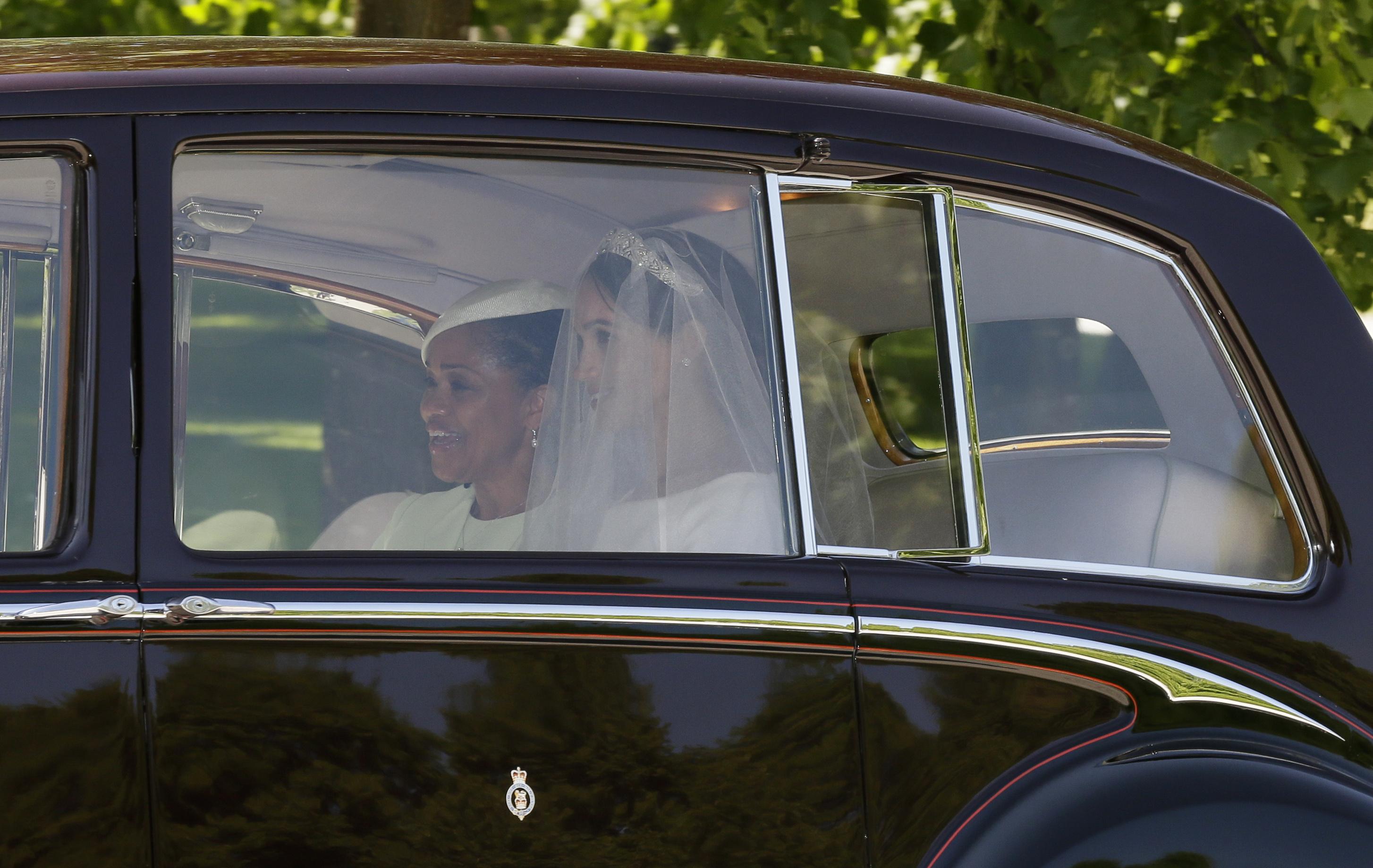 Meghan dejó en estas primeras fotos un indicio de su vestido, uno de los secretos mejor guardados de la boda. (Foto: AP)
