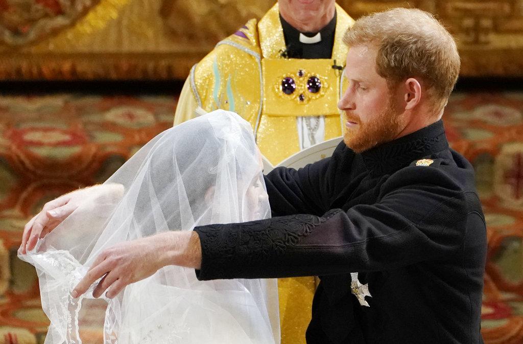 El príncipe Harry retira el velo del rostro de su aún prometida ante el altar. (Foto: AP)