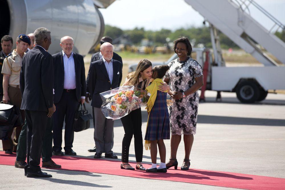 La primera dama de Haití, Martine Moise (derecha) y una niña reciben a la reina Letizia (izquierda) a su llegada a Puerto Príncipe, en el marco de su viaje para conocer proyectos de cooperación española. (AP)
