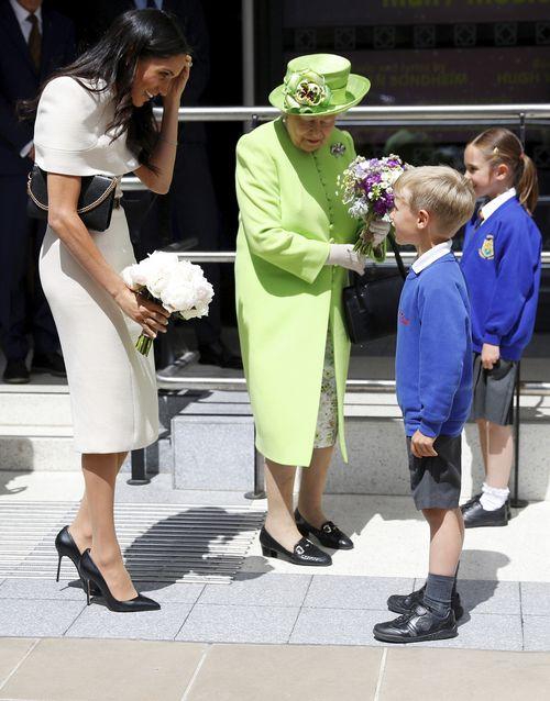 Varios niños reciben a Meghan y Elizabeth II a su llegada al Storyhouse Chester. (Foto: AP)