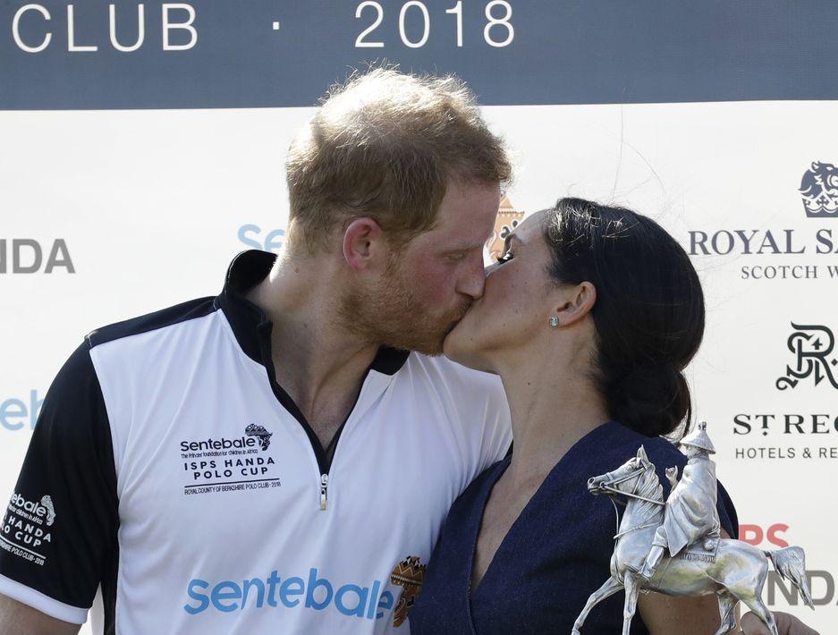 Los duques de Sussex se dan un beso en la ceremonia del Sentebale ISPS Handa Polo Cup. (AP)