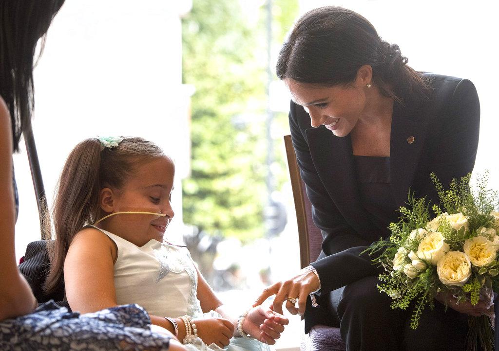Meghan Markle conversa y consiente a Matilda Booth, de 7 años, durante la gala de WellChild. (Foto: AP)