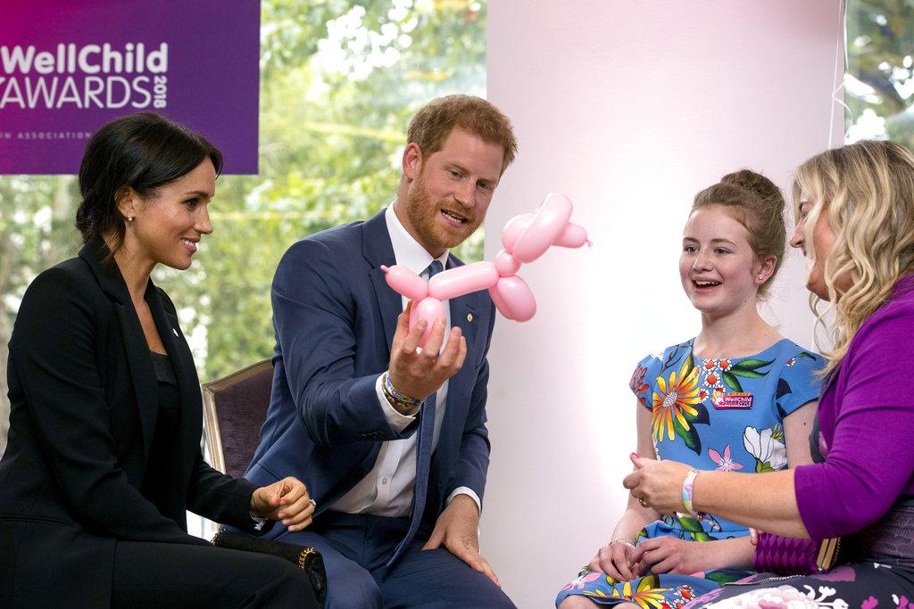 El príncipe Harry y Meghan Markle conversan y juegan con un perrito de bomba junto a Poppy y su madre Jayne en la gala anual de WellChild. (Foto: AP)