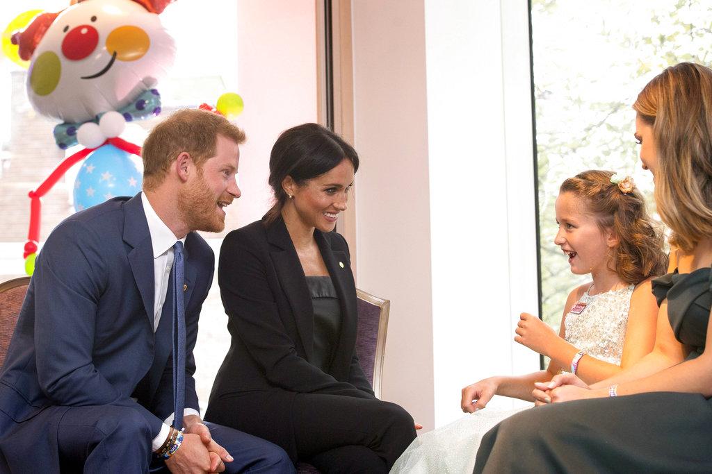 Meghan Markle y el príncipe Harry, padrino de la ong WellChild conversan con Chloe Henderson y su hermana Hana en la gala anual en Londres. (Foto: AP)