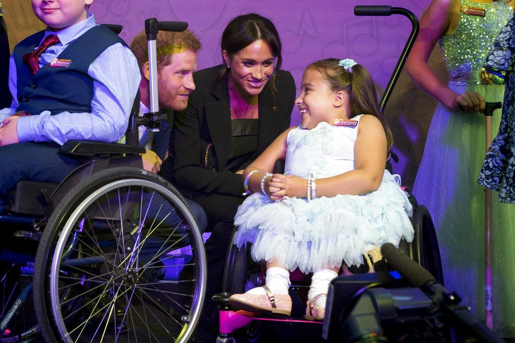 Meghan Markle y el príncipe Harry saludan a Matilda Booth, de 7 años, durante la gala de WellChild. (Foto: AP)