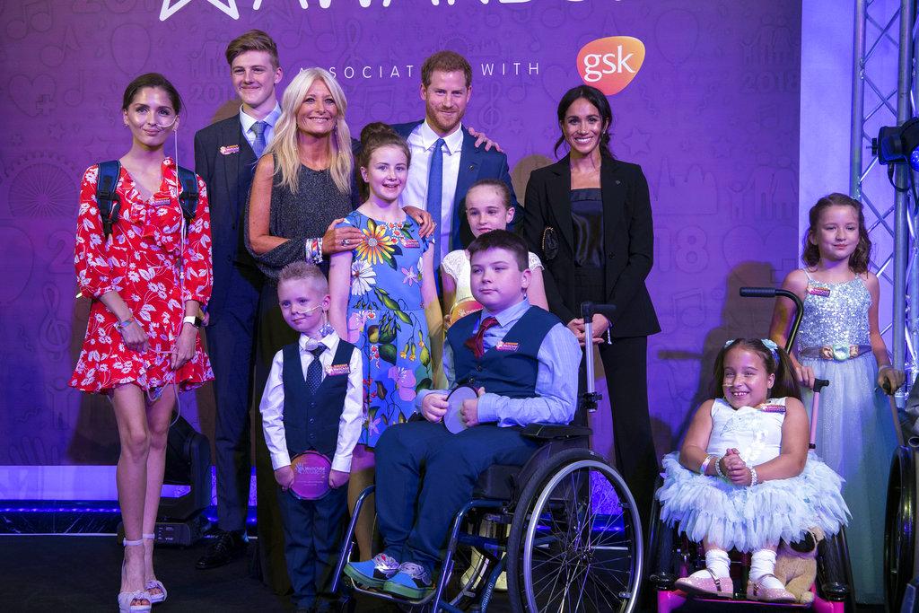 El príncipe Harry, padrino de la ong WellChild, y su esposa Meghan, junto a un grupo de niños en la gala anual de la entidad. (Foto: AP)
