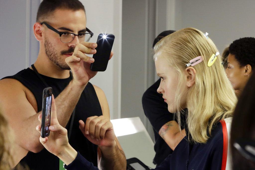 Un maquillista toma foto fotos a una modelo antes de salir a la pasarela de Tory Burch. (Foto: AP)