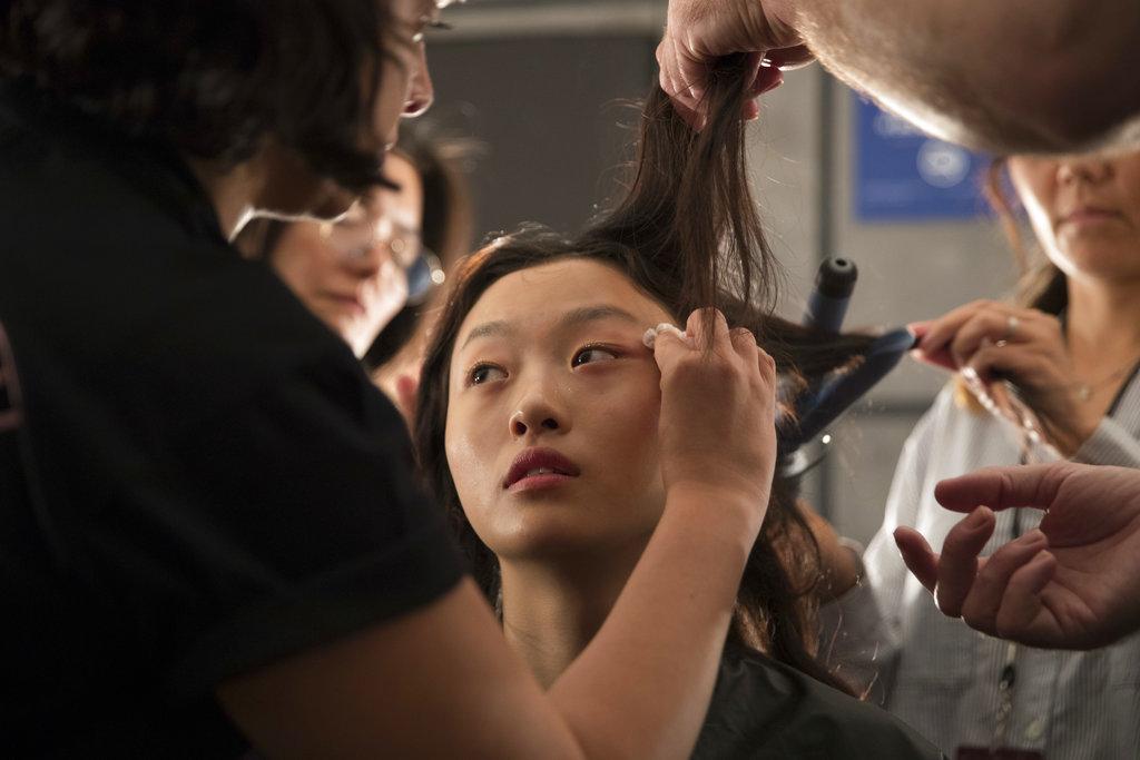 Un maquillista trabaja sobre el rostro de una modelo antes de presentar la colección primavera/verano 2019 de Milly. (Foto: AP)