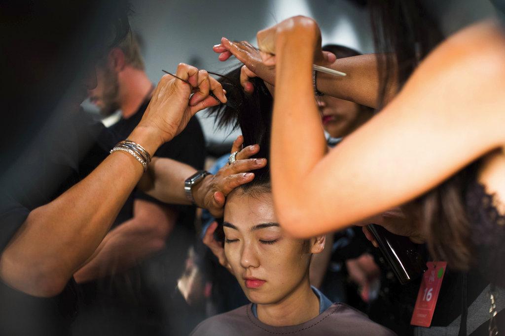 Dos estilistas trabajan en una de las modelos del desfile de The Blonds que lleva como tema a las villanas de Disney en el NY Fashion Week. (Foto: AP)