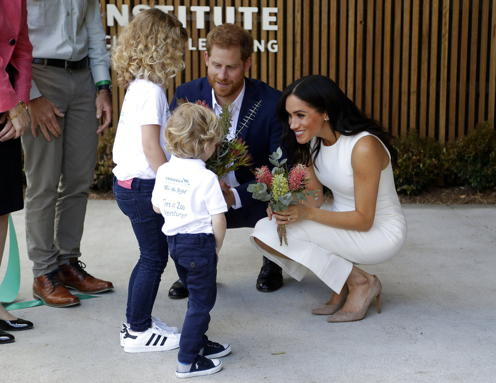 El príncipe Harry y Meghan Markle reciben un ramo de flores de manos de Finley Blue and Dasha Gallagher en el Taronga Zoo de Sidney, uno de los sitios que visitaron en Australia. (Foto: AP)