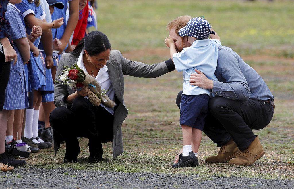Luke Vincent, de 5 años, juega con la nariz del príncipe Harry mientras Meghan Markle tiene un gesto de cariño con los dos a su llegada a Dubbo, Australia. (Foto: AP)