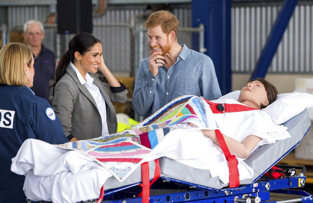 Los duques de Sussex observan un equipo de entrenamiento que simula a una paciente embarazada mientras asisten a la presentación de un nuevo avión sanitario en el Aeropuerto Regional de Dubbo. (Foto: Ap)