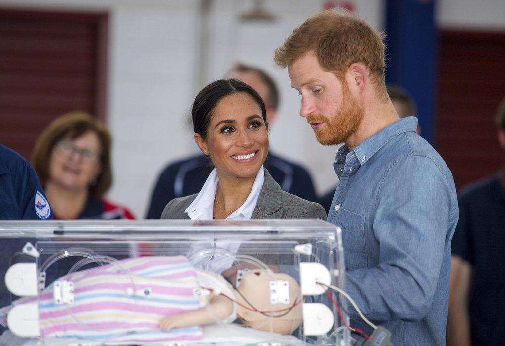 Meghan observa con una gran sonrisa a su esposo mientras les enseñan un equipo de entrenamiento que simula a un bebé en una incubadora mientras asisten a la presentación de un nuevo avión sanitario en el Aeropuerto Regional de Dubbo. (Foto: Ap)