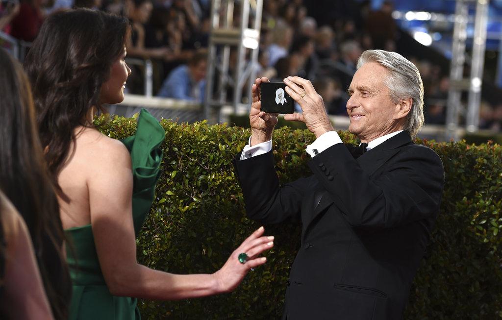 Michael Douglas toma una foto a Catherine Zeta-Jones en los Golden Globe, premio que entrega la Asociación de la Prensa Extranjera de Hollywood. (Foto: AP)