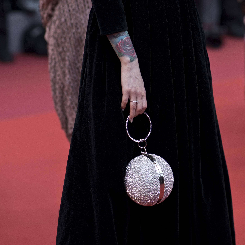 """Una de las invitadas al estreno de """"A Hidden Life"""" llamó la atención con esta cartera en forma de esfera metálica. (Foto: AP/Petros Giannakouris)"""