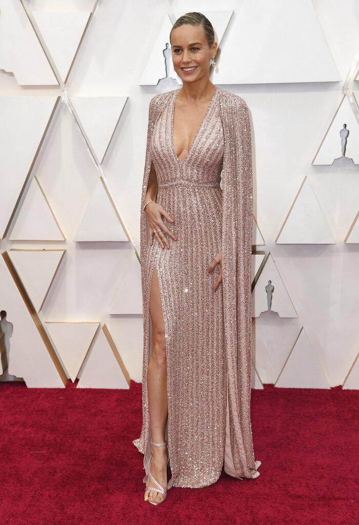 Brie Larson también llevó capa larga sobre un escotado vestido en tono rosado con detalles metálicos, de Celine. (AP)