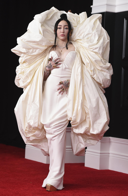 Noah Cyrus habló con los periodistas con un vestido Schiaparelli color crema con un enorme efecto de capa que le rodeaba la cara. (AP)