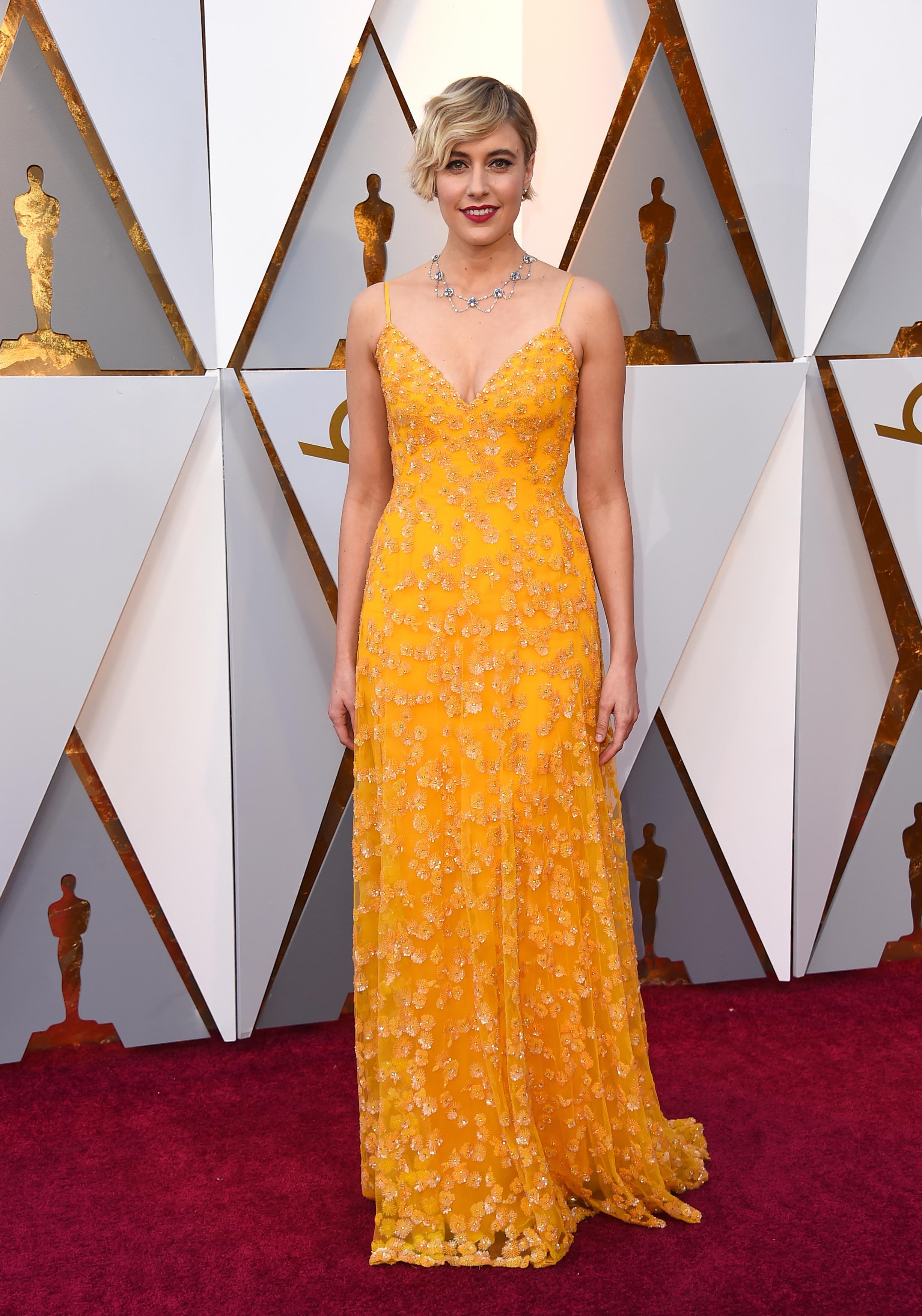 Greta Gerwig, nominada al Oscar en las categorías Mejor director y Mejor guión original, luce un vestido en tono amarillo intenso de Rodarte , uno de los colores de 2018. (The Associated Press)