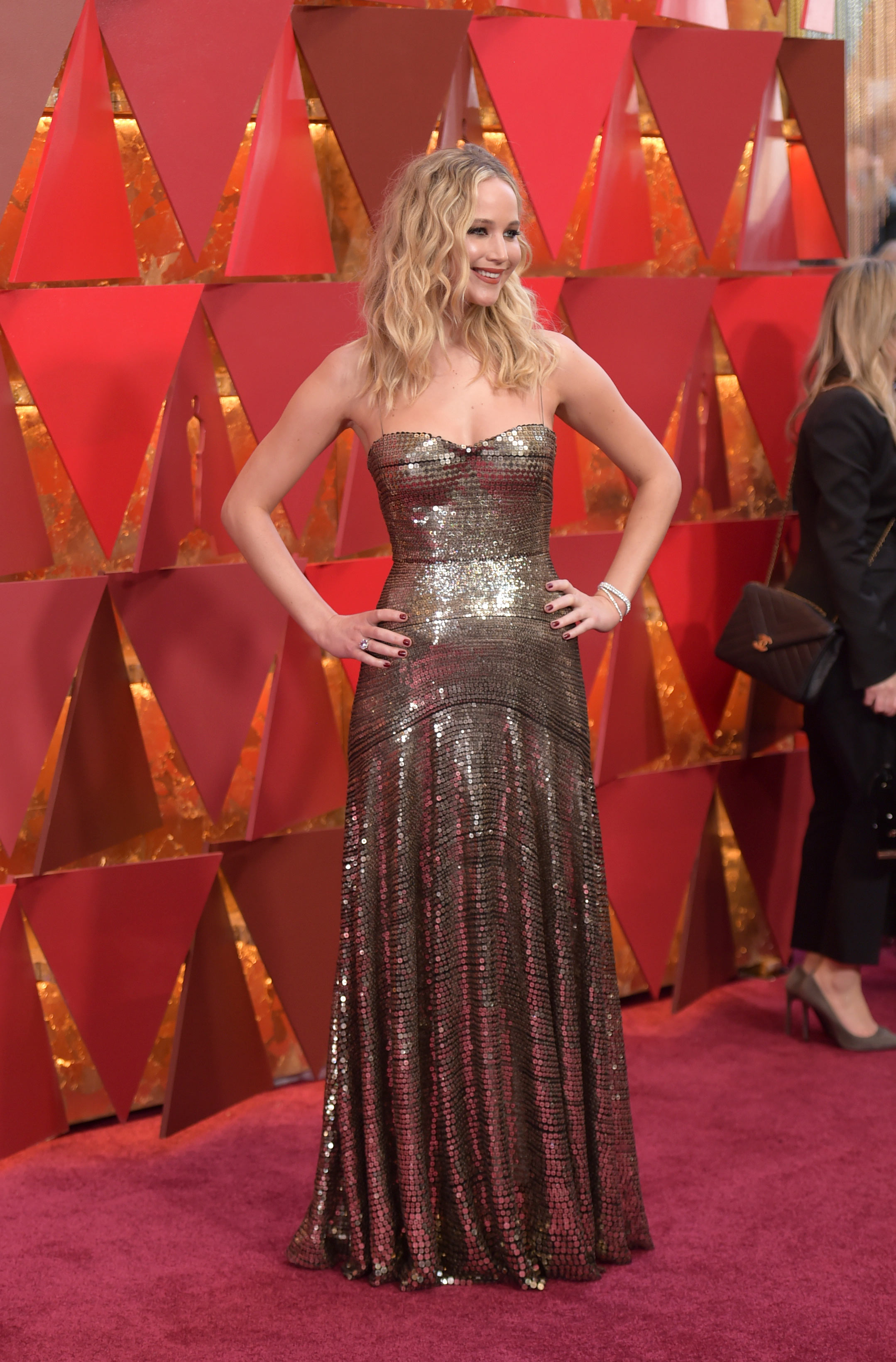 Jennifer Lawrence en un vestido de Dior, también en tonos metalizados, una de las tendencias de la alfombra roja de los Oscar 2018. (The Associated Press)