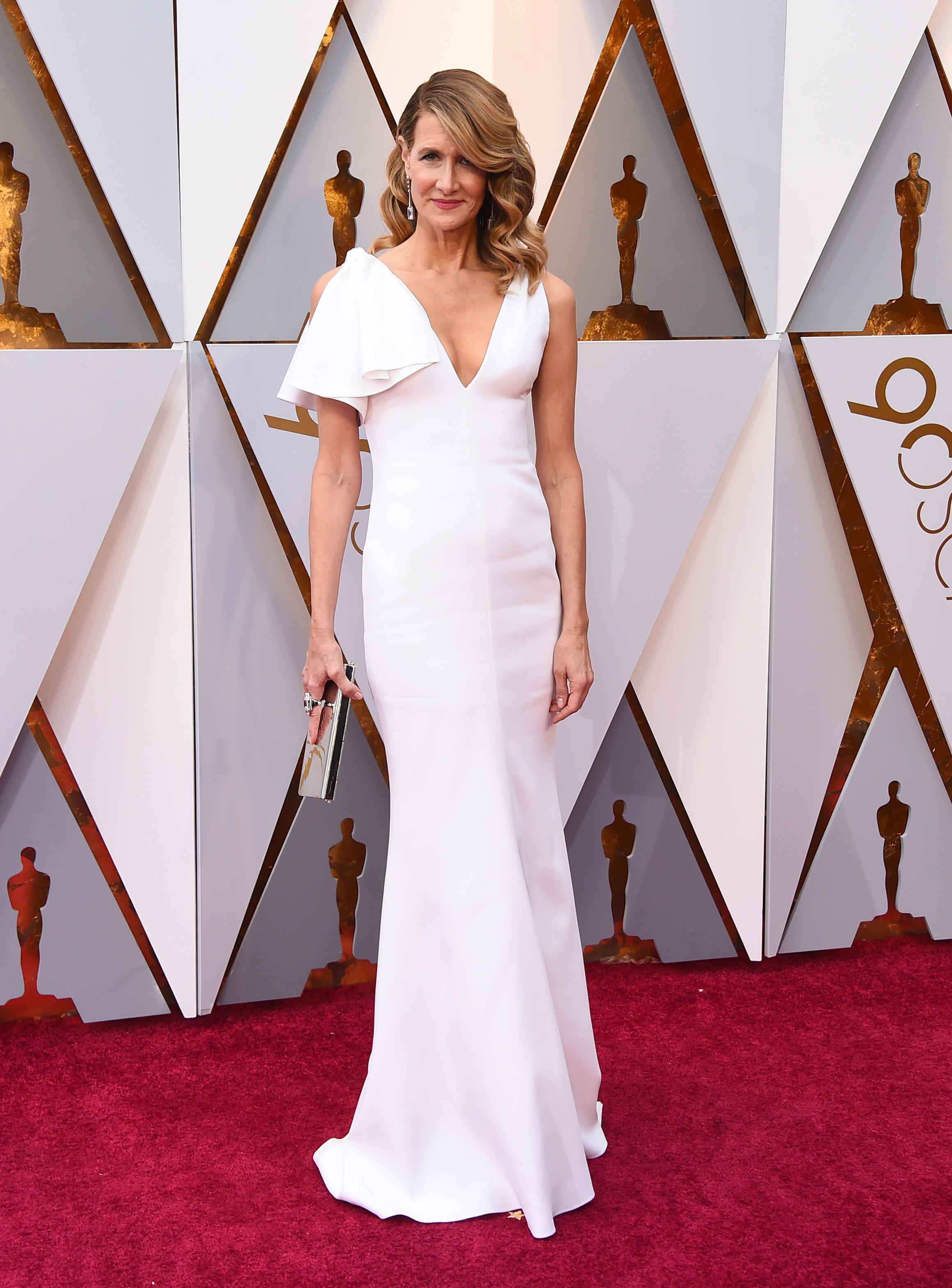 Laura Dern luce un elegante vestido blanco de Calvin Klein su llegada a la entrega de los premios Oscar de 2018. (The Associated Press)