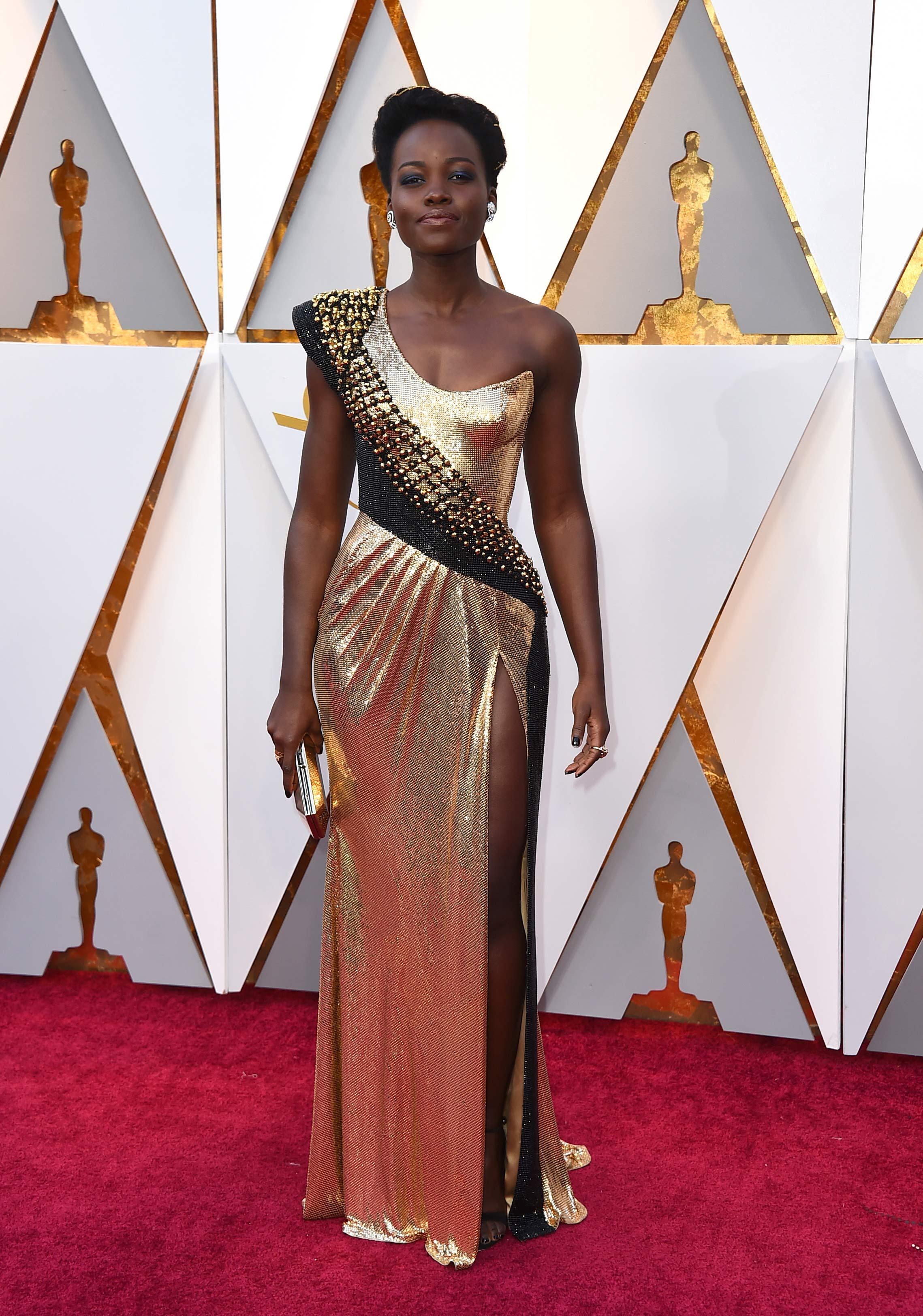 Lupita Nyong´o fue otra de las actrices que eligió un vestido en tonos metalizados, de la firma Versace, para la ceremonia de los Oscar. (The Associated Press)