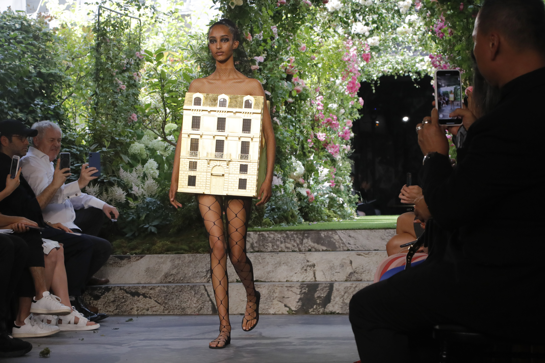"""Evocando la arquitectura más literalmente fue el aspecto final: Una modelo desnuda """"usando"""" una réplica del edificio del taller de Dior hecho en hoja de oro. (AP)"""