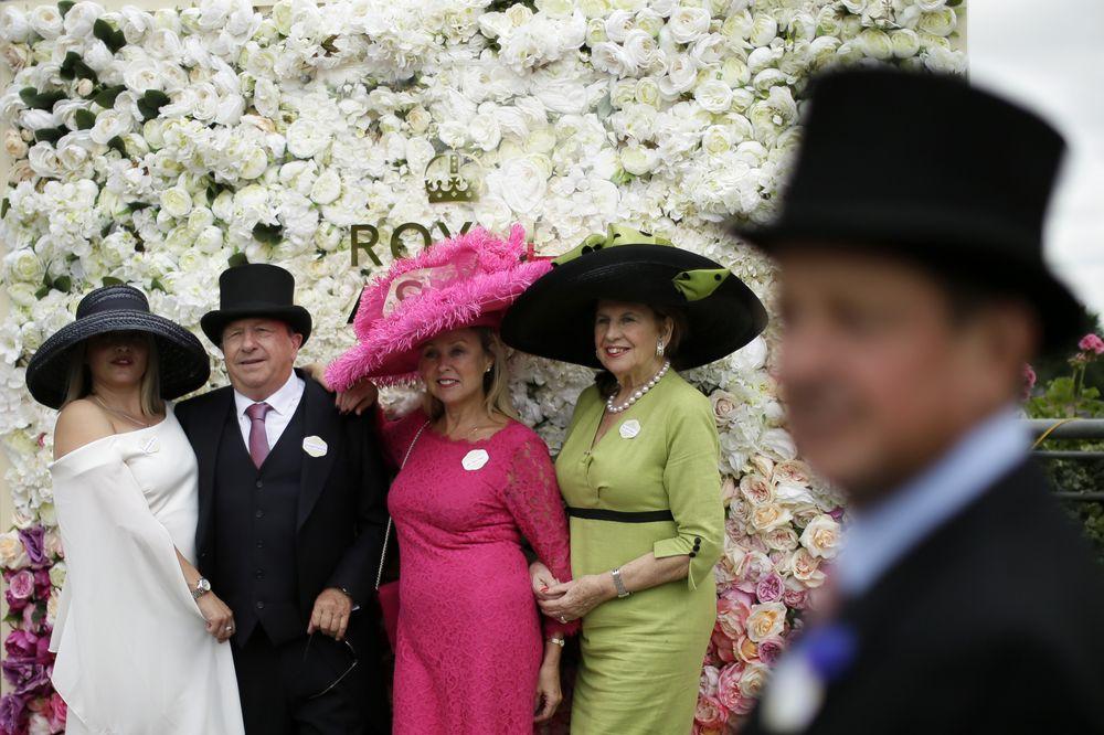 Tres invitadas lucen sus sombreros de gran diámetro, y de distintas tonalidades en el espectro. (Foto: AP)