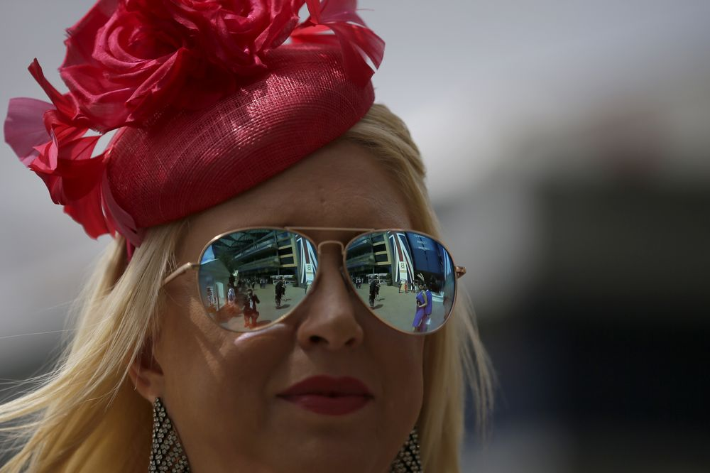 """Una espectadora lleva puesto un sombrero de tamaño """"petite"""", resaltado con rosas color rojo escarlata en la parte superior. (Foto: AP)"""