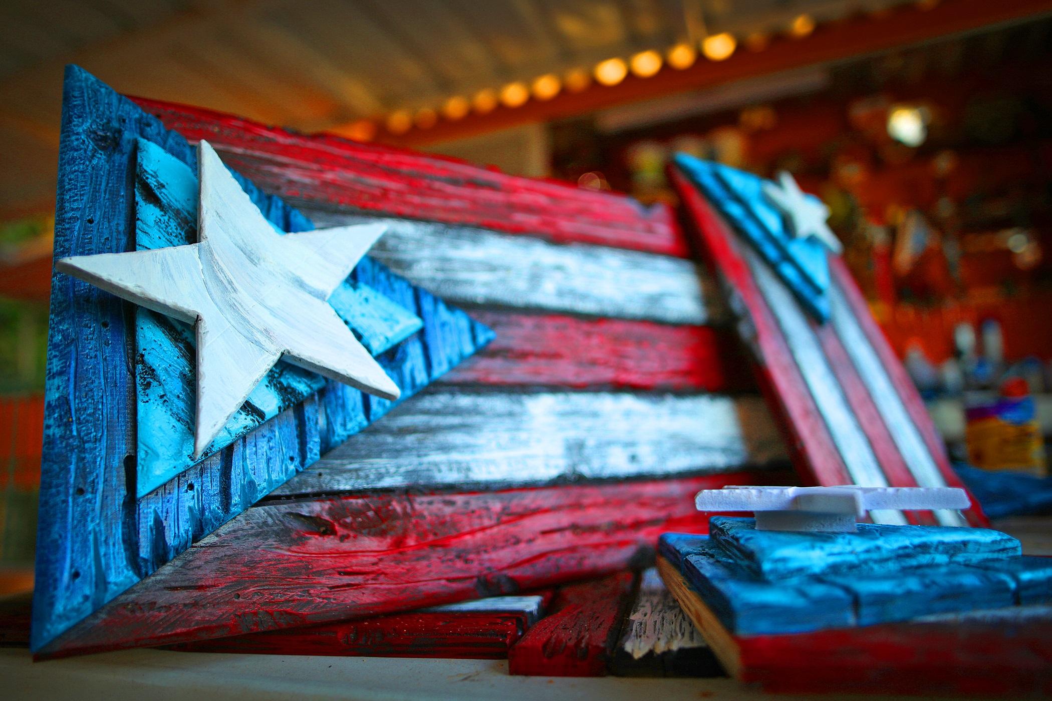 Banderas artesanales hechas en madera por el artista puertorriqueño Juan Luis Martínez Torres. Cada pieza es tallada, cortada y marcada profunda en cada franja para presentarla con mucha fuerza, por lo que obtendrá una pieza de arte única. Banderas disponibles en distintos tamaños. www.BanderasArtesanales.com (Suministrada)