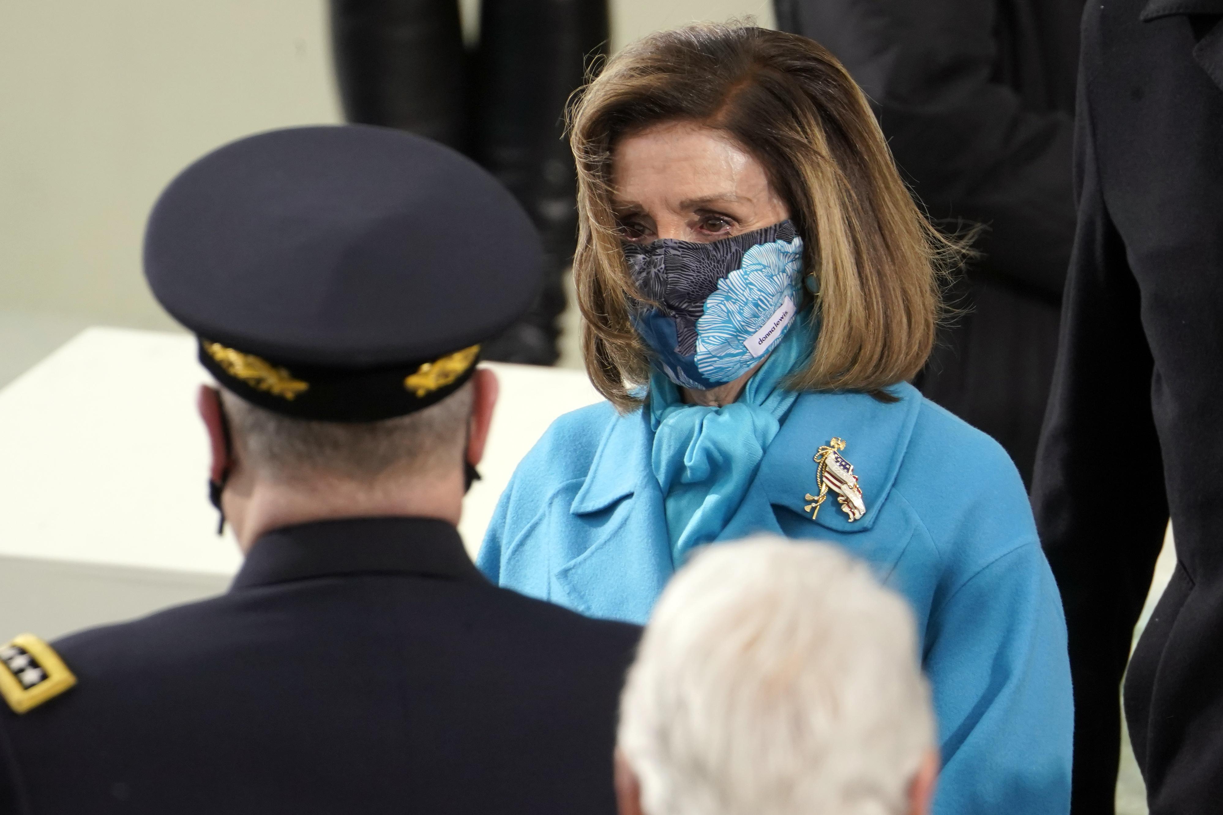 """La """"speaker"""" de la Cámara, Nancy Pelosi fue otra que seleccionó el azul como el color ideal para la ceremonia. Y, para darle un toque muy personal, no dejó de llevar un llamativo broche dorado y mascarilla estampada. (AP)"""
